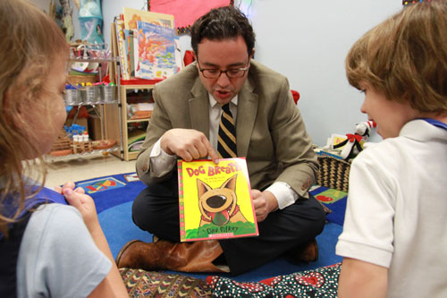 Photo of young professional reading to children at the Center for Excellence in Early Education