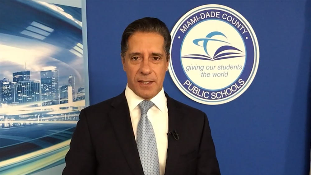 Miami-Dade Public Schools Superintendent standing in front of a Miami-Dade County Public Schools logo